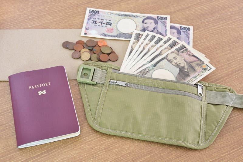 Billetes de banco japoneses con el pasaporte en bolso de la cintura foto de archivo