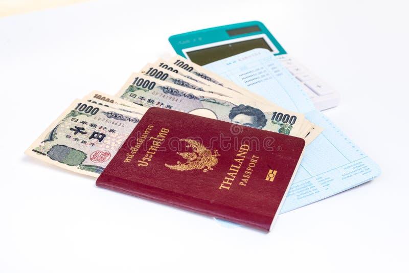 billetes de banco japoneses de los yenes de la moneda en pasaporte y calculadora en w imagen de archivo
