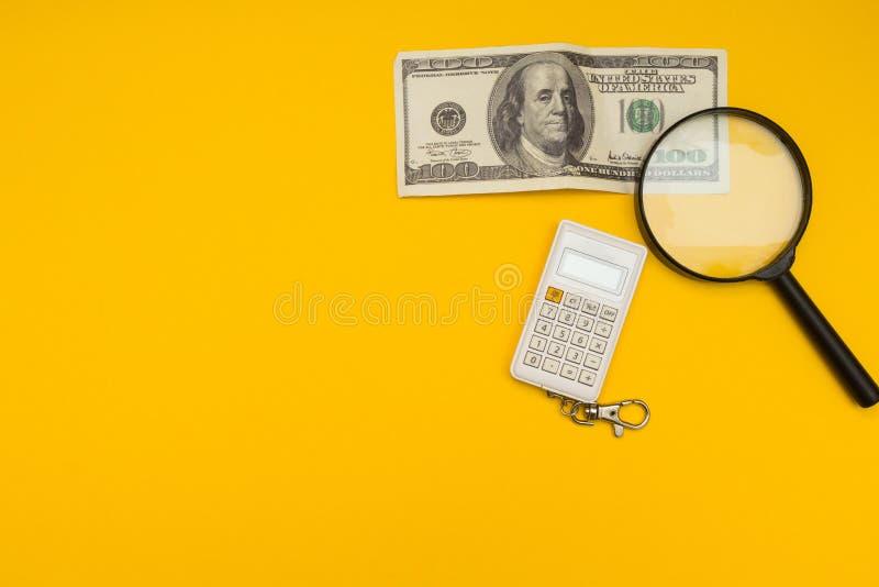 100 billetes de banco, lupas y calculadoras del dólar americano imagen de archivo libre de regalías