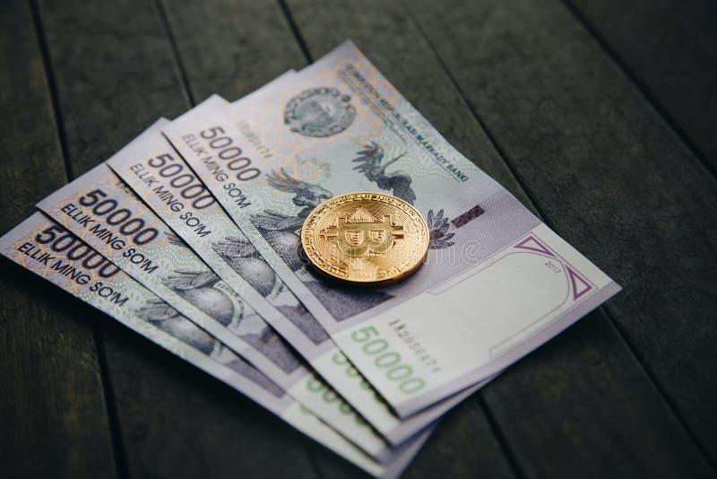 Billetes de banco y Bitcoin del Uzbek Cincuenta mil sumas del Uzbek fotos de archivo
