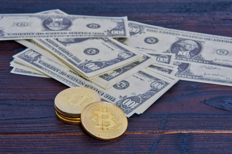 Billetes de banco y Bitcoins del dólar en una tabla fotos de archivo