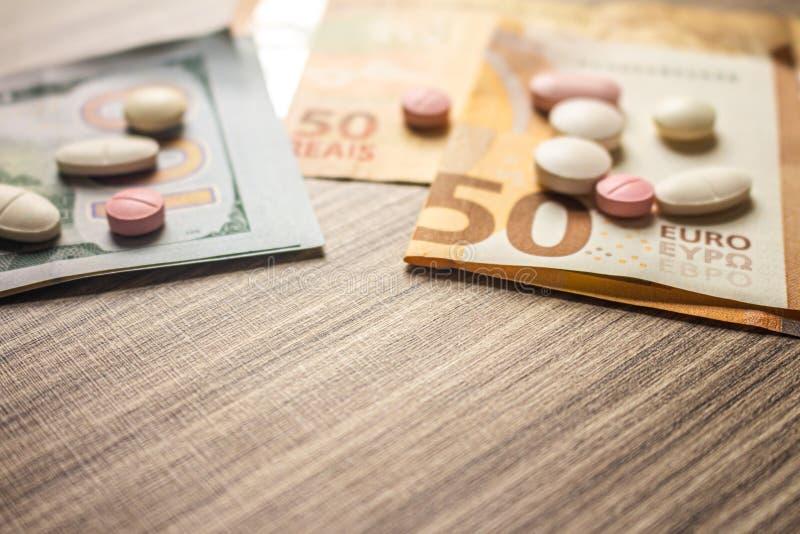 Billetes de banco y medicinas en un escritorio Concepto del coste de la salud Dinero y drogas para el uso legal imágenes de archivo libres de regalías