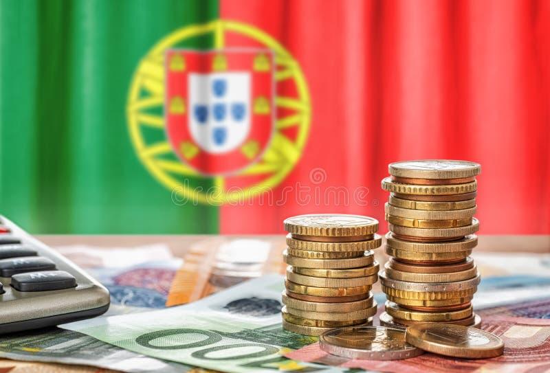 Billetes de banco y monedas euro delante de la bandera nacional de Portug imagen de archivo libre de regalías