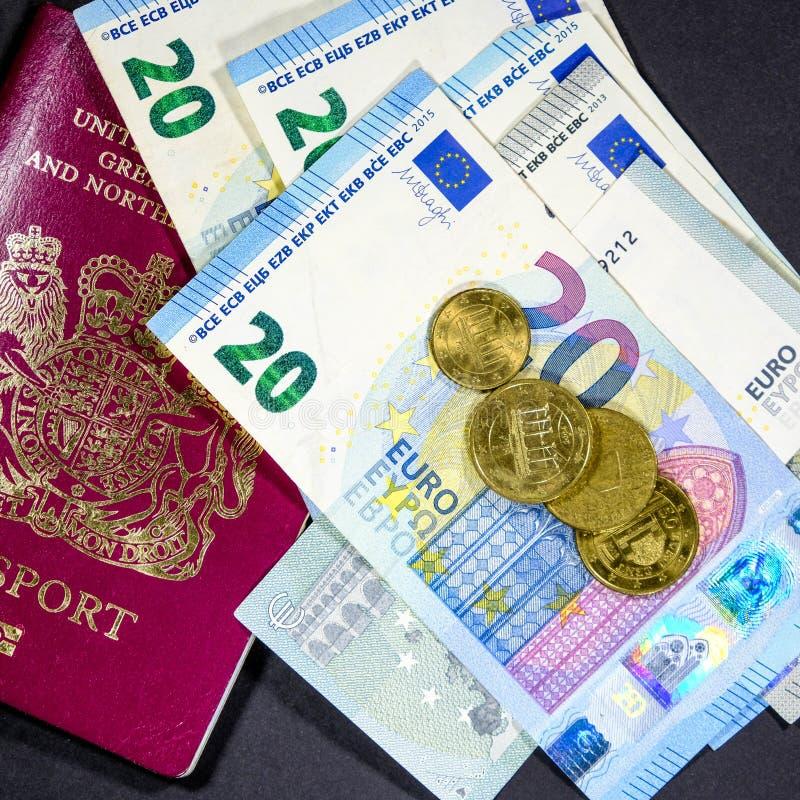 Billetes de banco y monedas euro de la moneda con un pasaporte británico foto de archivo