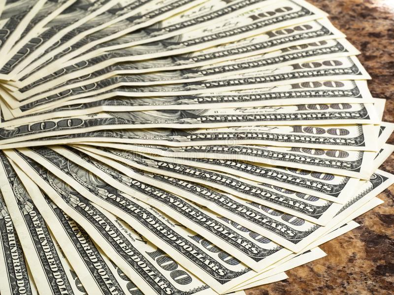 100 billetes de dólar apilados en la tabla fotografía de archivo