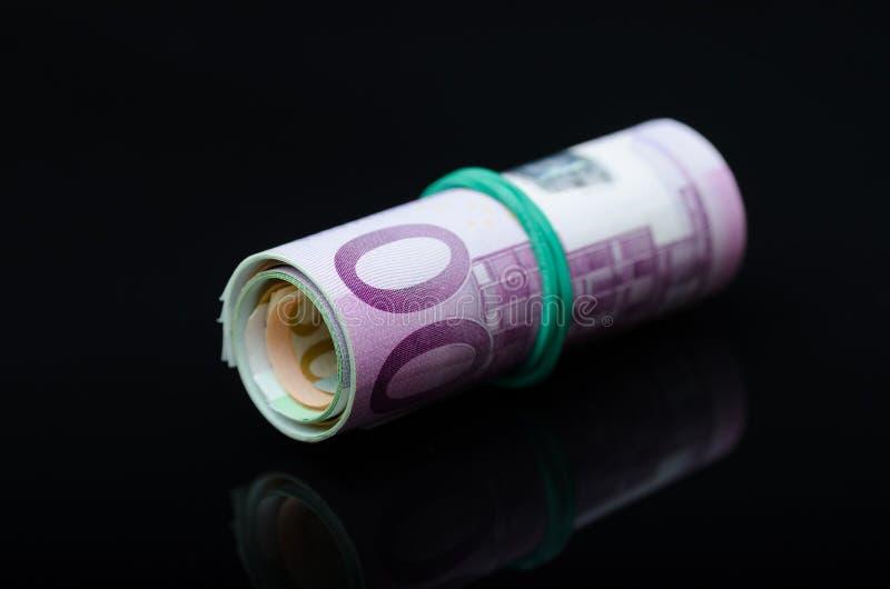 Billetes europeos en rollo en fondo negro fotografía de archivo