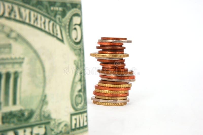 Billetes y columna de monedas imagen de archivo libre de regalías