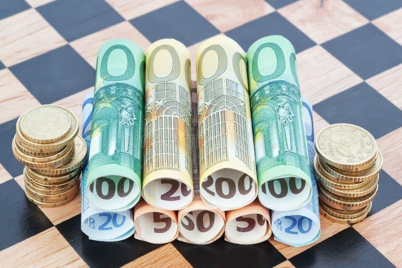 Billetes y monedas como el euro en el tablero de ajedrez. fotografía de archivo libre de regalías