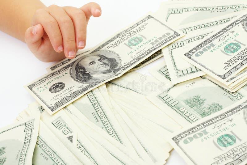 Billets d'un dollar américains de hunderd de la main et de l'argent des enfants image libre de droits