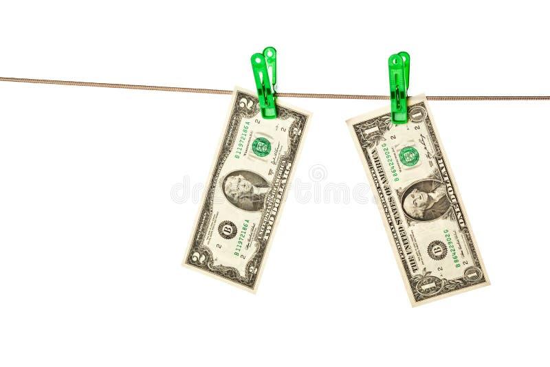 Billets d'un dollar goupillés à une corde à linge image libre de droits