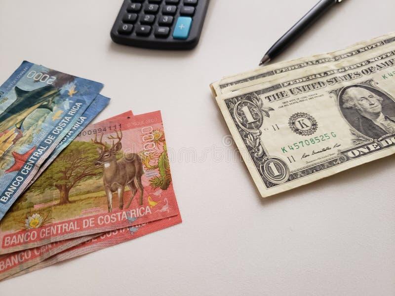 Billets de banque de Costa Rican, billets d'un dollar un américains, calculatrice et stylo noir sur le fond blanc photo libre de droits