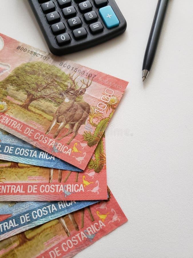 Billets de banque de Costa Rican, stylo noir, calculatrice et fond blanc photographie stock libre de droits