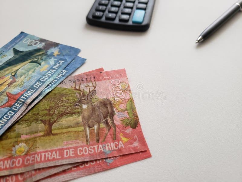 Billets de banque de Costa Rican, stylo noir, calculatrice et fond blanc photographie stock