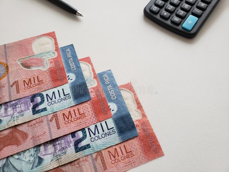 Billets de banque de Costa Rican, stylo noir, calculatrice et fond blanc image libre de droits