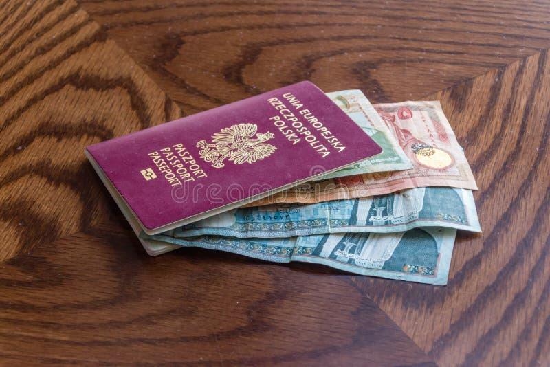 Billets de banque de dinar jordanien à l'intérieur de passeport biométrique polonais photos libres de droits