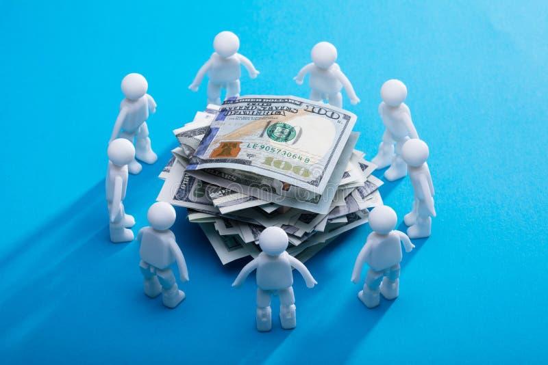 Billets de banque empilés entourés par les figures humaines images libres de droits