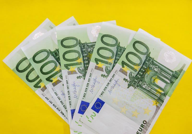 Billets de banque de 100 euros sur un fond jaune, en gros plan photographie stock libre de droits