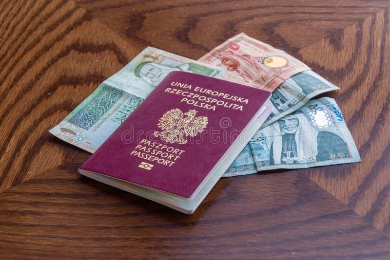 Billets de banque de passeport biométrique polonais et de dinar jordanien photographie stock libre de droits
