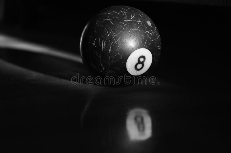Billiard ball. A nice billiard ball rolls away on the dark desk royalty free stock photos