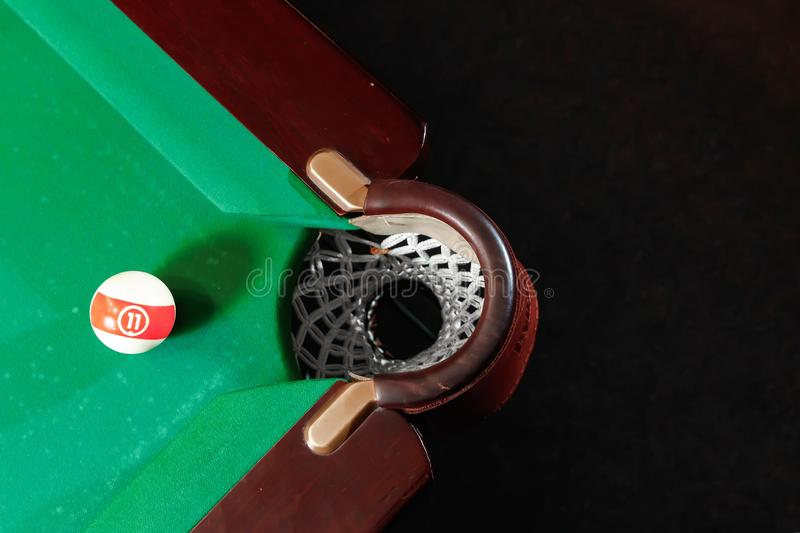 Billiard ball near the pockets on the billiard table, top view, American billiards. Sports games, outdoor activities.  stock image