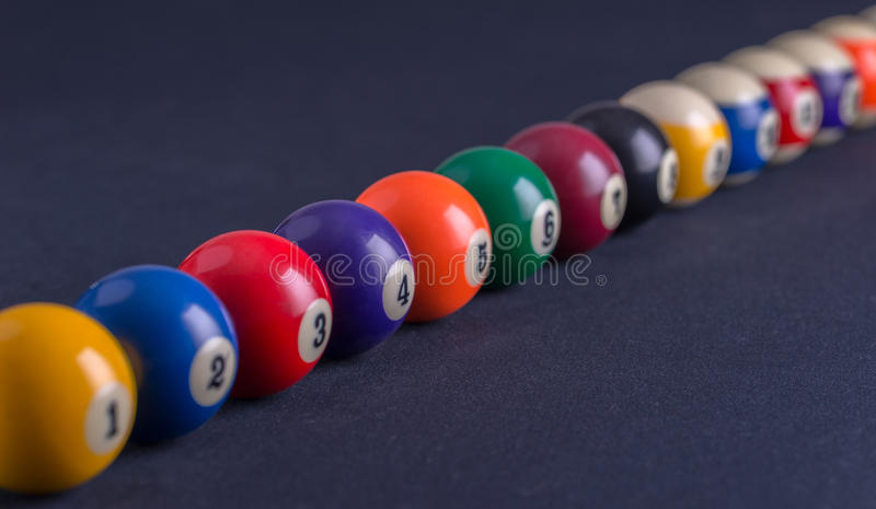Billiard balls in a row on blue table. stock photo