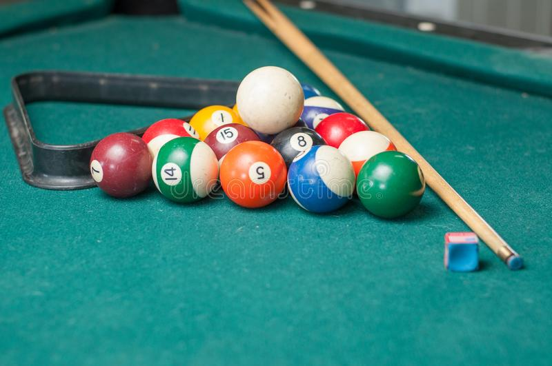 Billiard balls and a stick on a green table. Billiard balls isolated on a green background stock photo