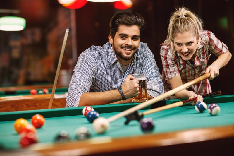 Billiard game- couples playing pool game royalty free stock photos