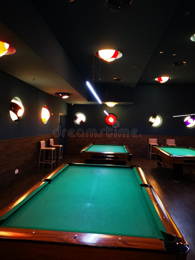Billiard room - tables and light sources. In the shape of a billiard ball stock photo