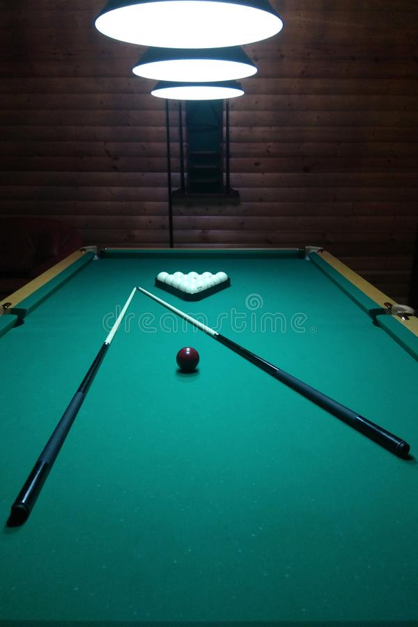 A billiard table has several layers and a cue stock photos