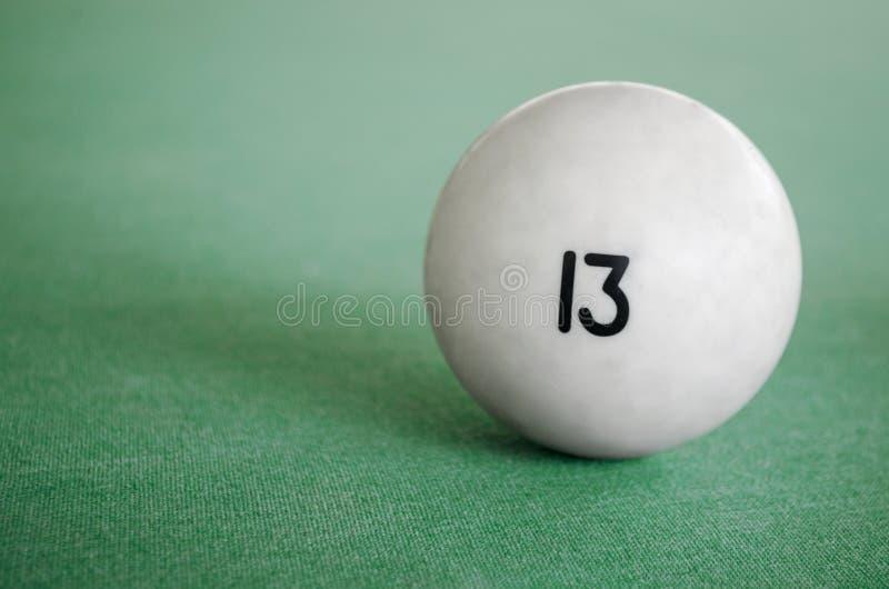 Billiardboll nummer 13 på en pöltabell En närbildbild av en boll för nummer tretton på en pöltabell arkivbilder