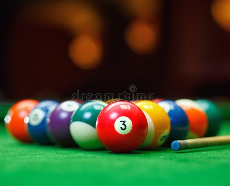 Billiardbollar i en grön pöltabell royaltyfri bild