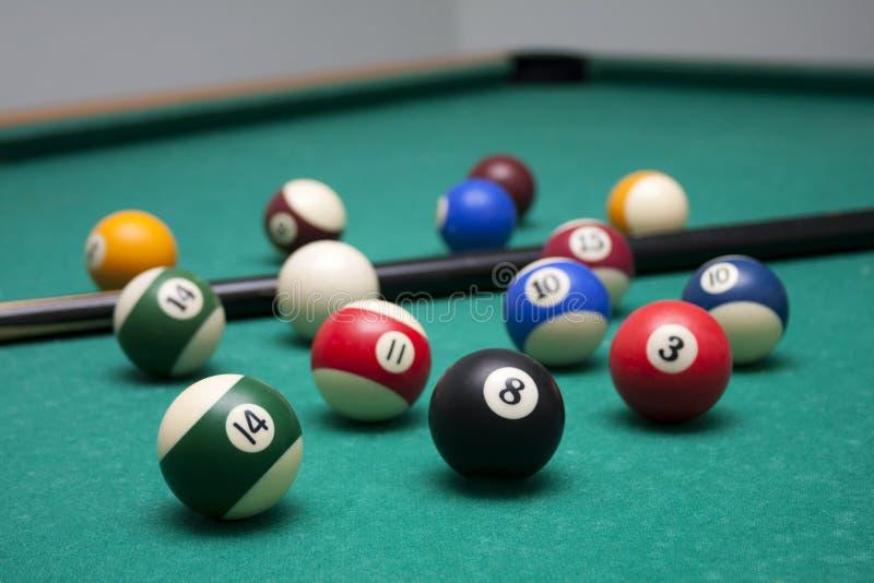 Billiardbollar och en stickreplik i en fritidklubbamiljö, massor av biljard på tabellen, tapetbakgrund royaltyfria bilder