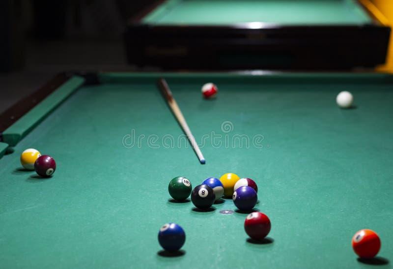 Billiardbollar p? den gr?na tabellen med billiardstickreplik arkivbilder