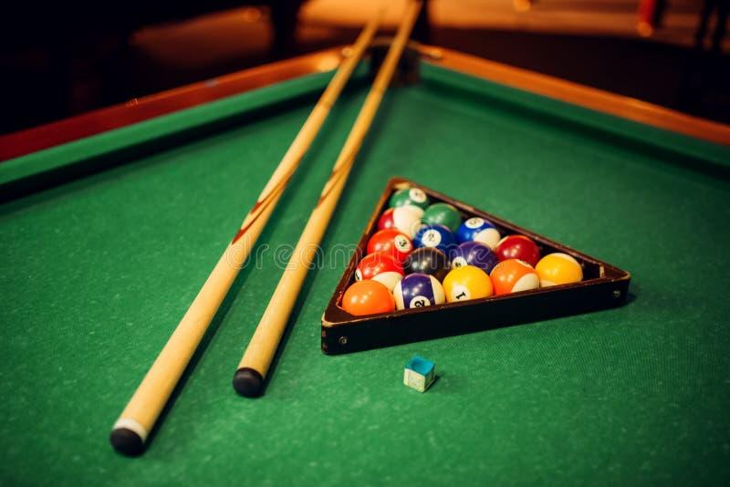 Billiardbollar, stickreplik och pyramid på den gröna tabellen arkivbilder