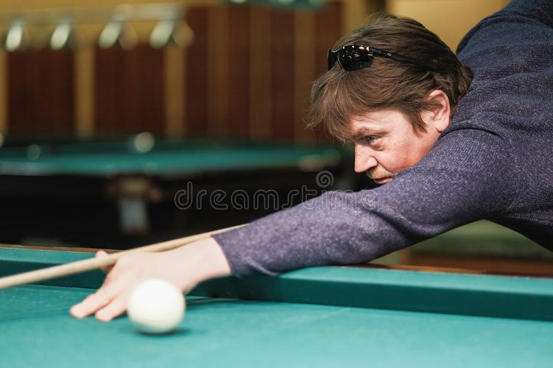 A pool player takes aim at the ball royalty free stock image