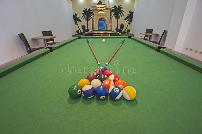 Billiards pool table in a games room. Closeup of billiard balls on green felt table with pool cues in games room stock photos