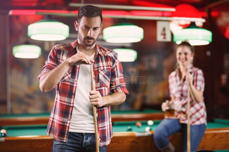 Billiardspelaren gnider krita hans stickreplik-barn som mannen spelar billiard arkivbild