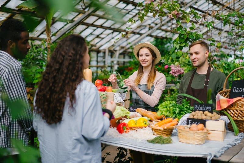 Billiga försäljare som säljer ekologiska grönsaksörter till köpare på marknaden royaltyfri fotografi