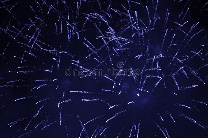 Billiga mousserande fyrverkerier, med en ogenomskinlighet, vit-blått, mot natthimlen fotografering för bildbyråer