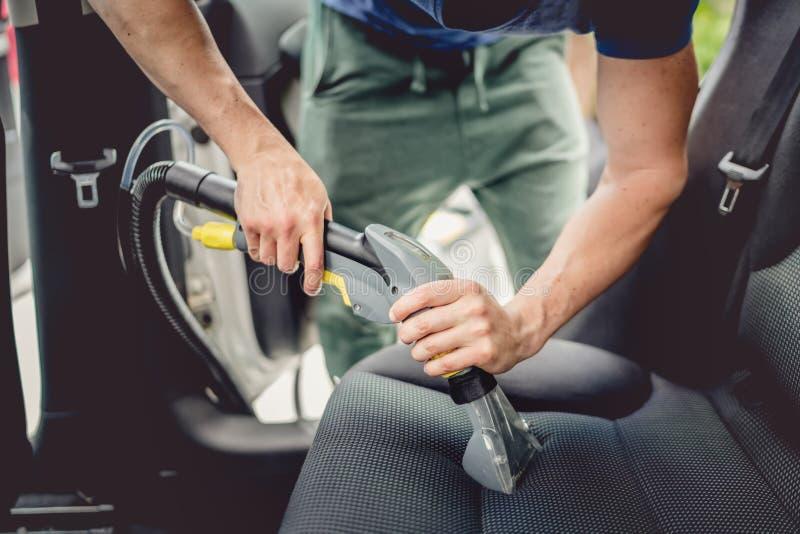 Billokalvård - manligt användande yrkesmässigt ångavakuum för smutsig bilinre arkivbilder