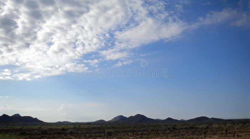 Billowy Desert Clouds Above the Mountains royalty free stock images