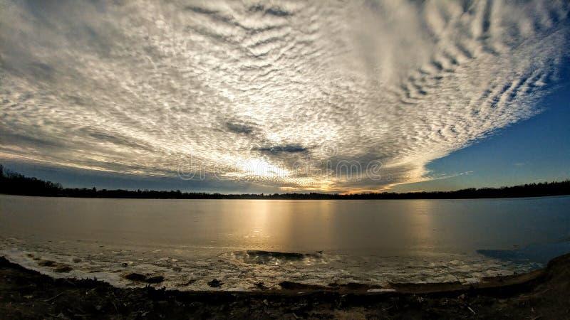 Billowy Wolken über dem See mit goldenem Licht stockbild