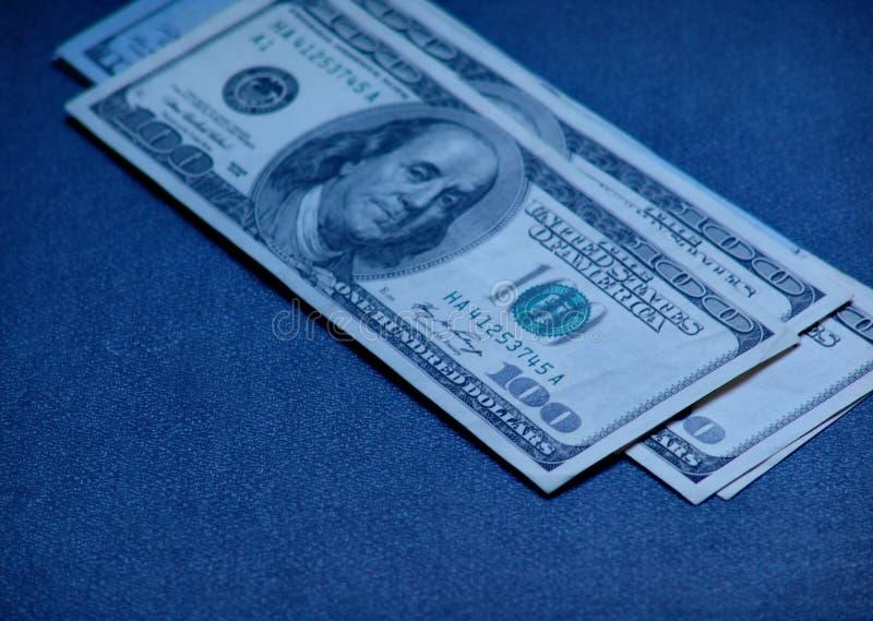 $ 100 bills. 100 dollar bills closeup on a blue background side view stock photo