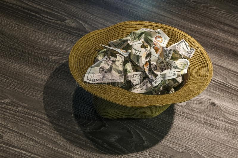 $100 bills in hat. US currency $100 bills in mans hat stock images