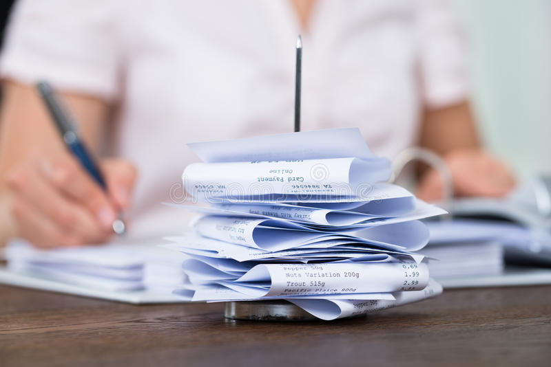 Bills In Paper Nail With Businessperson At Desk. Close-up Of Bills In Paper Nail With Businessperson Working At Desk In Office royalty free stock photo