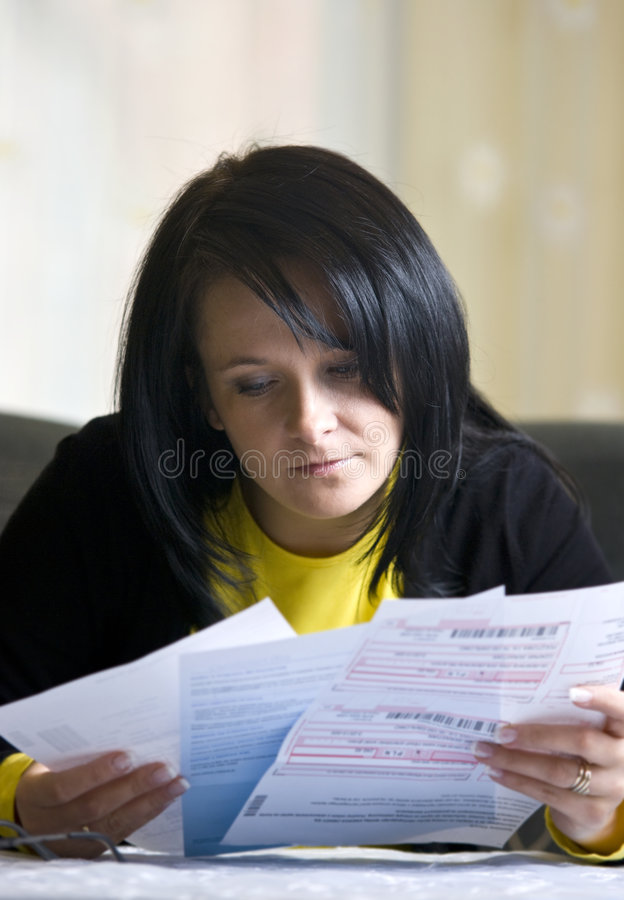 Bills to pay. A brunette woman sitting at the living room table, looking with concern at her monthly bills to pay royalty free stock image