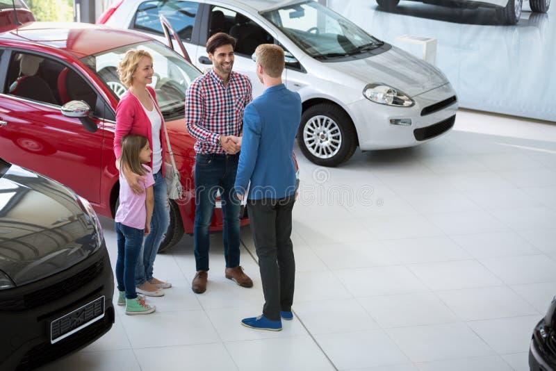 Bilmedlet gratulerar familjen på köpandebilen royaltyfria foton