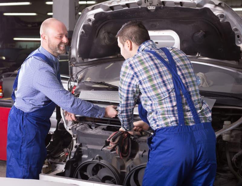 Bilmekaniker som arbetar på carshop fotografering för bildbyråer