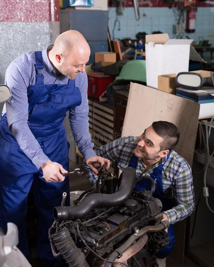 Bilmekaniker som arbetar på carshop royaltyfri foto