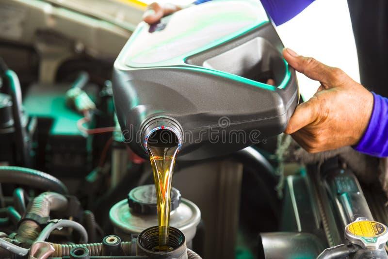 Bilmekaniker som byter ut och häller ny olja in i motorn på strömförsörjningen arkivfoton